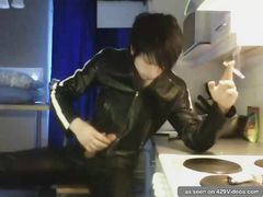 Leather-dressed punk youngster stroking off